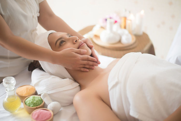 Midsection of therapist massaging young woman in spa