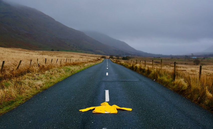 Raincoat On Road Amidst Landscape Against Sky