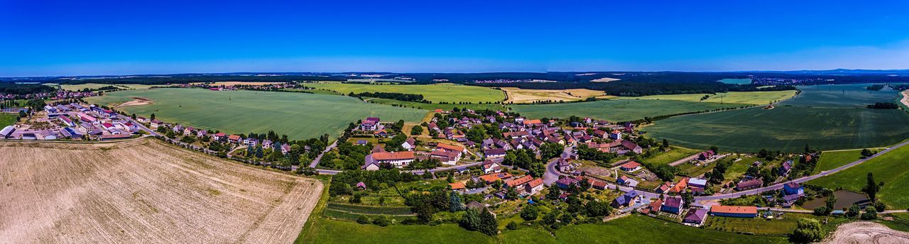 agriculture, rural scene, farm, landscape, high angle view, field, nature, beauty in nature, scenics, outdoors, green color, tranquil scene, day, aerial view, vineyard, patchwork landscape, blue, sunlight, built structure, no people, tree, building exterior, architecture, sky