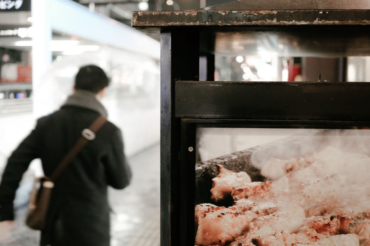 Close-up of meat in glass display with man walking in background