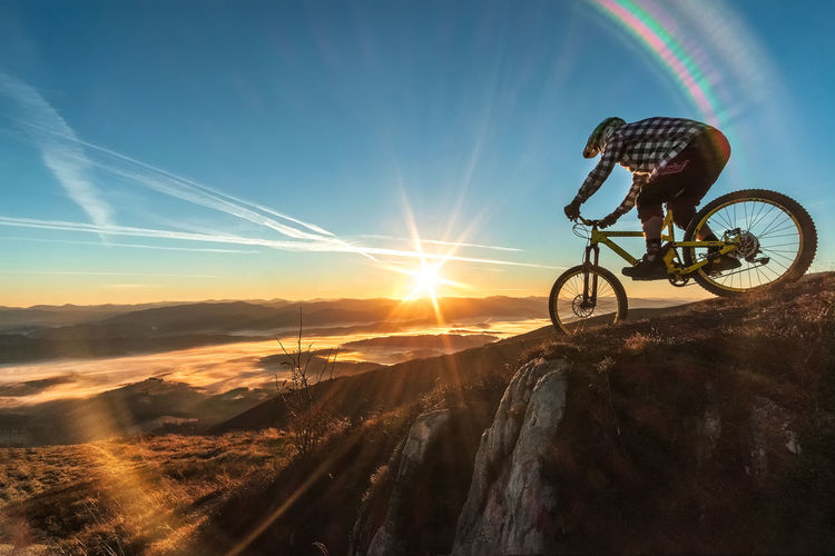 Bicycle on land against sky during sunset