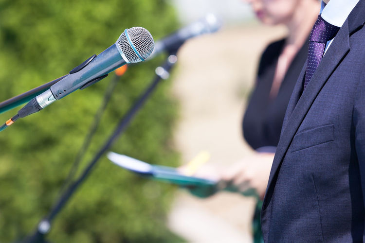Businessman or politician is giving a speech Corporate Event Speech Suit Broadcasting Business Businessman Giving A Speech Businessman In Suit Campaign Speech Close-up Information Input Device Media Media Event Microphone News Outdoors Politician Politician Giving A Speech Real People Speaking In Public Spokesperson Suit Tie Unrecognizable Person Vip