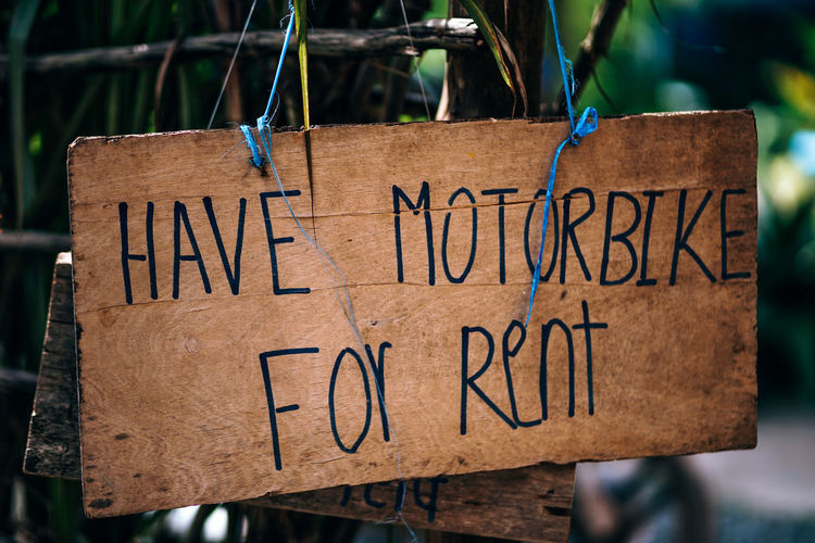 Wooden Have motorbike for rent sign. Sign is hanging with blue strings on a sunny street. Tropical background. Ad Hanging Hangs Motor Motorcycle RENT Road Sign Sunny Text Typography Wood Advertisement Bike Brown Rent Sign Rental Roadside Street Sun Symbol Tropical Wood - Material Wooden