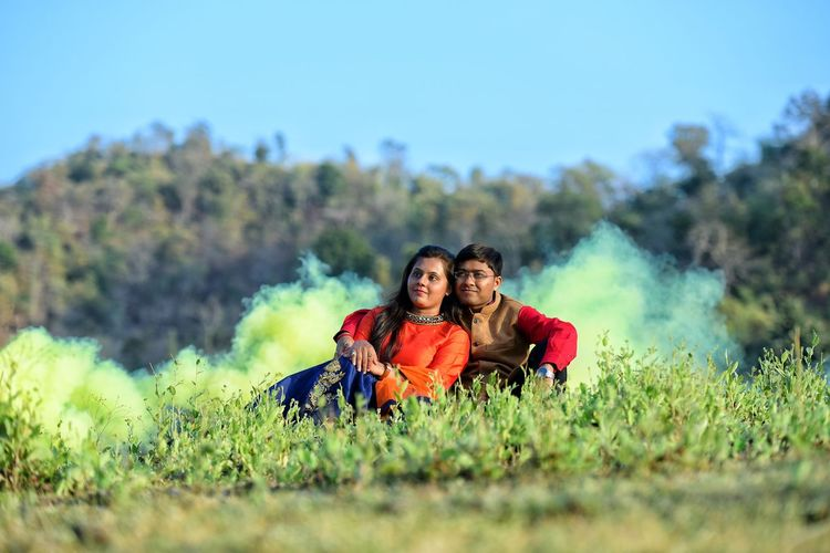 Couple Sitting On Grass Field Against Sky