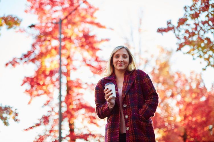 Autumn Beautiful Woman Beauty In Nature Casual Clothing Day Focus On Foreground Front View Happiness Holding Leaf Leisure Activity Lifestyles Looking At Camera Low Angle View Nature One Person Outdoors Portrait Real People Scarf Smiling Standing Tree Young Adult Young Women