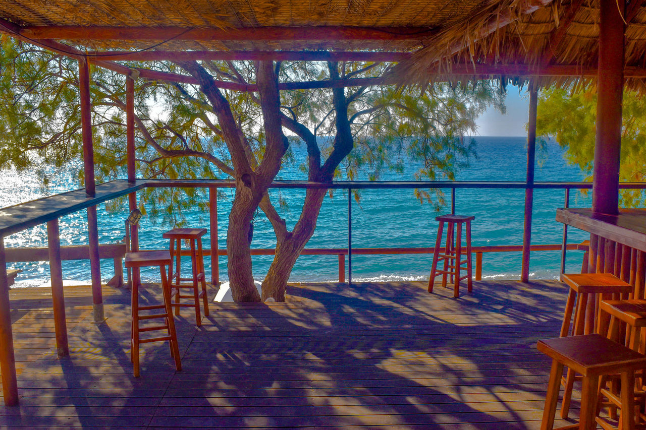 sea, luxury, vacations, wood - material, tourist resort, tranquil scene, nature, idyllic, porch, tropical climate, day, scenics, tranquility, luxury hotel, beach, travel, travel destinations, shadow, water, sunlight, no people, beauty in nature, architecture, outdoors, tree, wood paneling, holiday villa