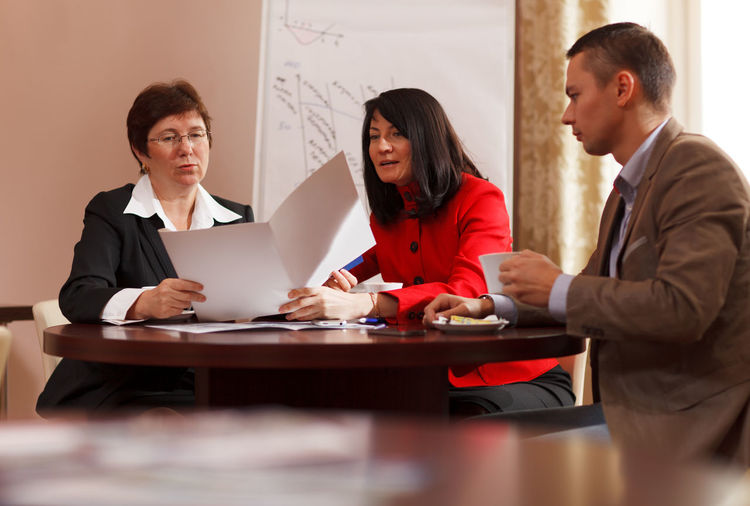 Smiling business colleagues working while sitting on table