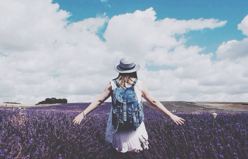 Rear view of woman standing in lavender field