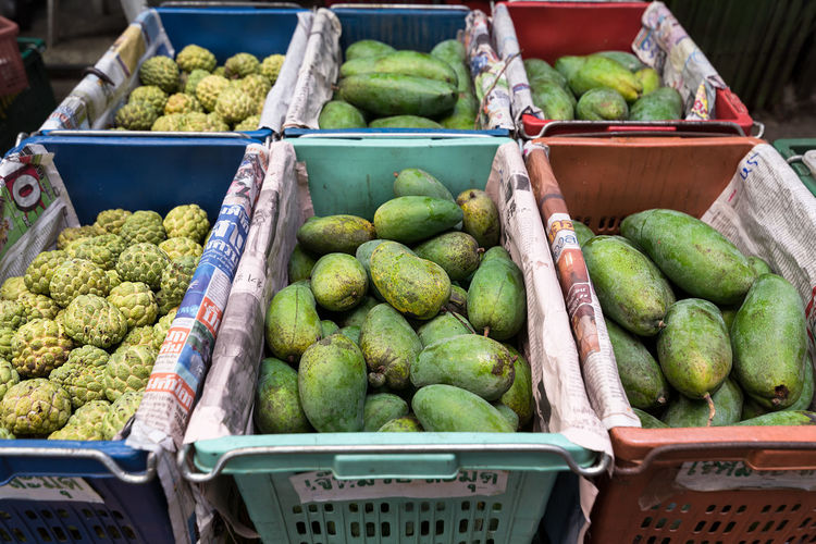 FreshCustard apples and green mangoes fruit boxed in plastic crates ready for wholesale at a Bangkok Market. Custard Apple Mangoes Abundance Basket Choice Crates Food Food And Drink For Sale Freshness Fruit Green Color Healthy Eating Large Group Of Objects Market Market Stall Outdoors Retail  Small Business Wholesale