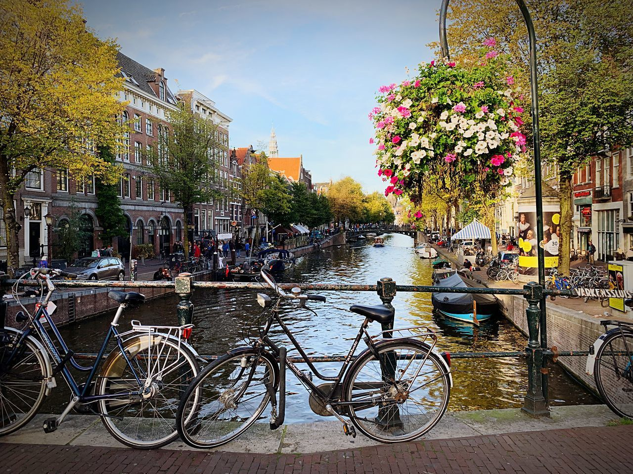 transportation, bicycle, building exterior, architecture, mode of transportation, built structure, city, water, plant, land vehicle, tree, nature, group of people, day, incidental people, canal, real people, sky, large group of people, outdoors