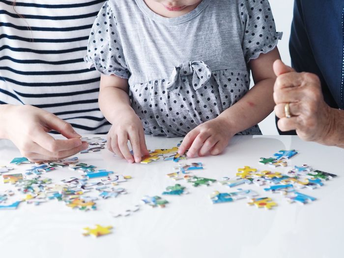 Midsection Of Family Playing Jigsaw Puzzle