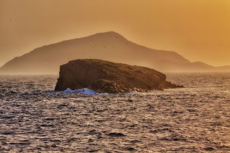 A rock in the sea in front of an island. Water Sea Beauty In Nature Rock Sky Scenics - Nature No People Waterfront Mountain Tranquil Scene Nature Sunset Rock - Object Tranquility Solid Land Non-urban Scene Remote Outdoors Island