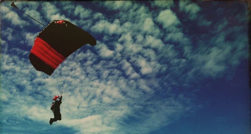 Panoramic view of person paragliding against sky