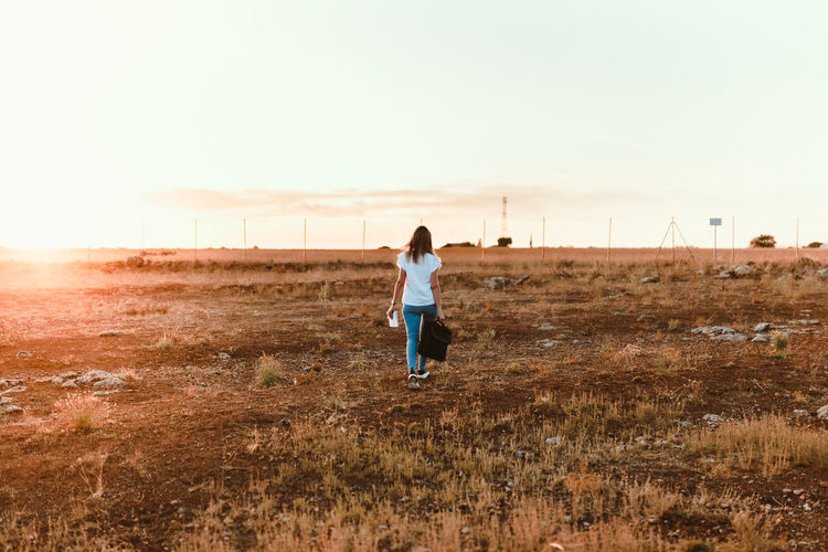 Rear view of woman walking on field against clear sky