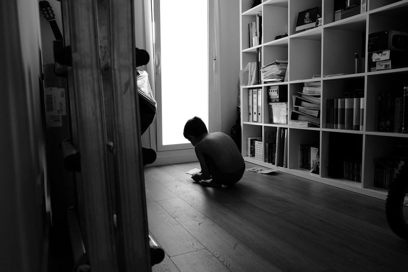 Shirtless boy crouching on hardwood floor by shelves at home