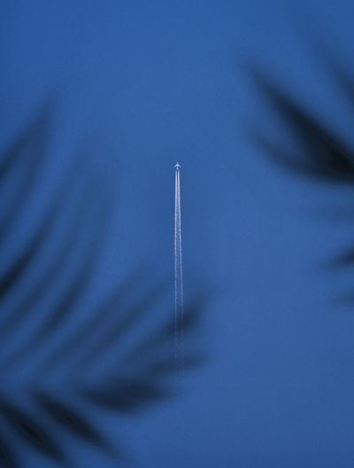 Close-up of airplane flying against blue sky