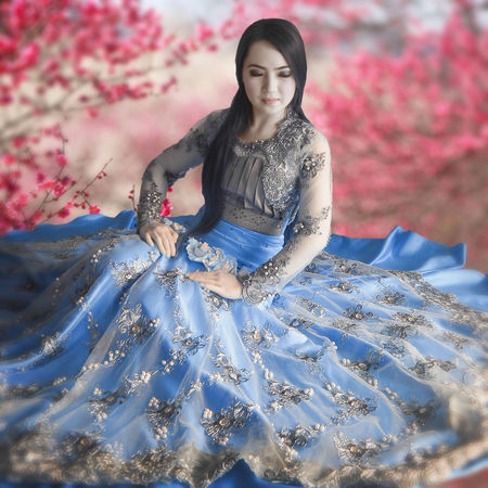 An infrared portrait of a young woman. Fashion Infrared Princess Sitting Beautiful Woman Blue Sky Color Infrared Front View Full Length Infrared 690nm Infrared Photography One Person Outdoors Potrait Real People Smile Traditional Clothing Young Adult Young Women