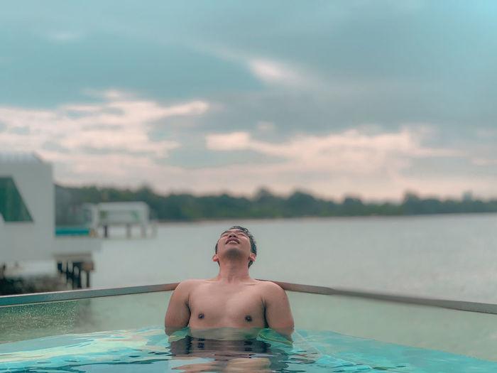 Shirtless man relaxing swimming in pool