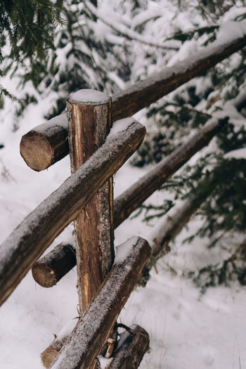 Close-up of wooden fence on snow covered land