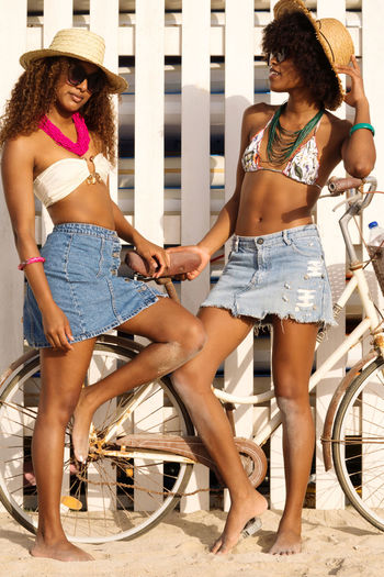 Two young black women having conversation at the beach smiling