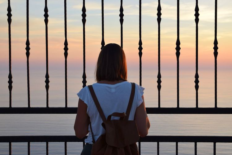 Rear view of woman looking at sea through railing against sky during sunset