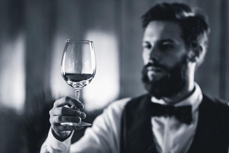 Bartendar looking at wineglass in bar