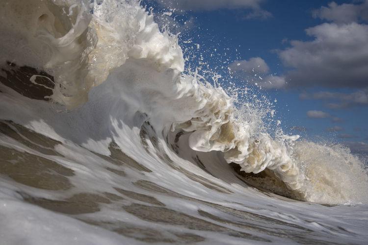 Close-up of sea waves splashing against sky