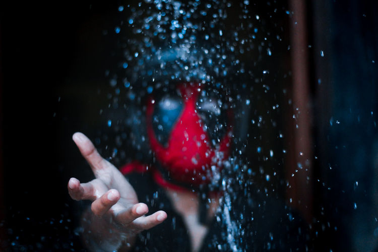 Man with mask reaching for falling water