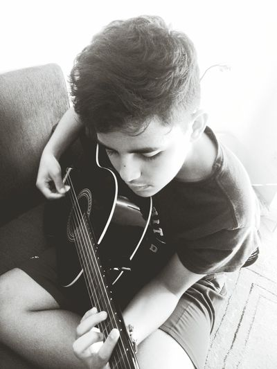 High Angle View Of Teenage Boy Playing Guitar At Home