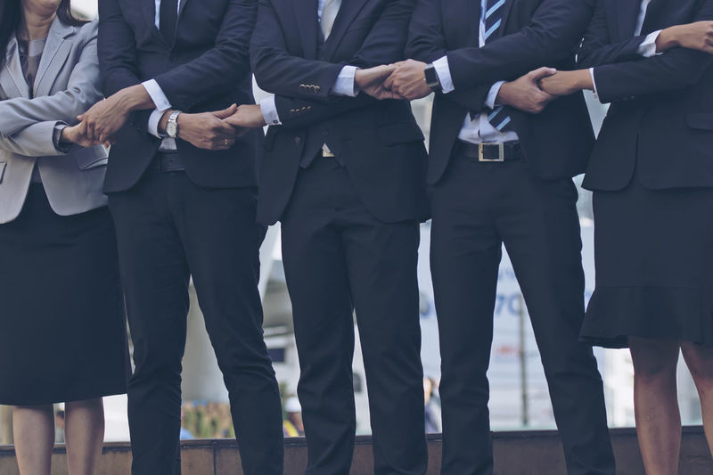 Midsection of business people holding hands standing outdoors