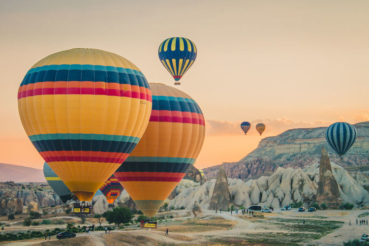 Multi colored hot air balloons flying over land