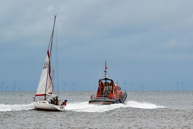 RNLI Lifeboat and a sailing school yacht with raised sails on the River Wyre estuary between Fleetwood and Knott End on Sea, Lancashire UK. Horizon Over Water Lifeboat Lifeboat RNLI Mast Nautical Vessel Outdoors RNLI Sailing Boat Sailing School Sailing Yacht Sails Sails Up Sailship Sea Seascape Sky Sky And Clouds Transportation Water Waves Wind Farm Yacht