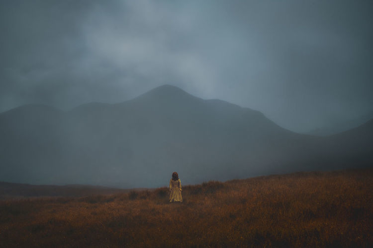 Rear view of woman standing on field against mountain during foggy weather