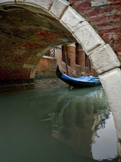 Gondola moored on grand canal seen through arch bridge