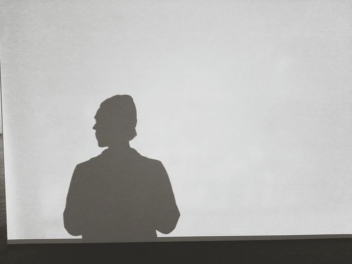 Shadow Of Man On Projection Screen In Darkroom