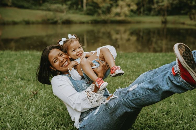 Cheerful mother playing with daughter while sitting at park