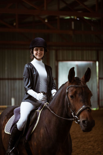 Portrait of smiling woman riding horse in stable