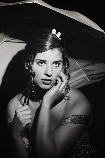 Close-up of young woman with umbrella in darkroom