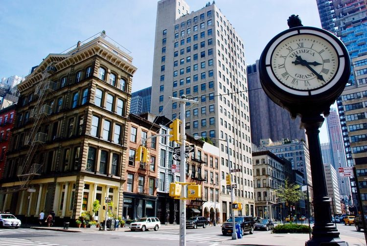 Low angle view of clock in city against sky