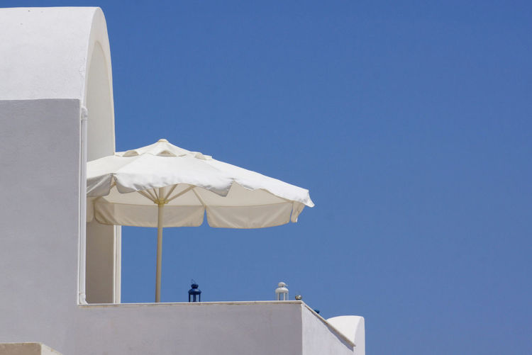 Low angle view of umbrella at balcony of building against clear blue sky