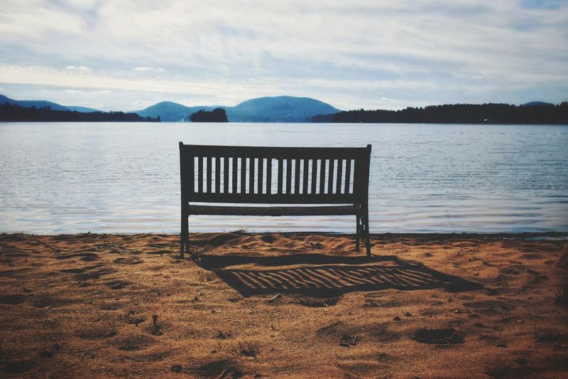 Empty bench on beach against sky and water