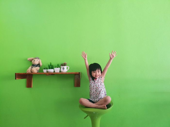 Smiling girl with arms raised sitting against green wall