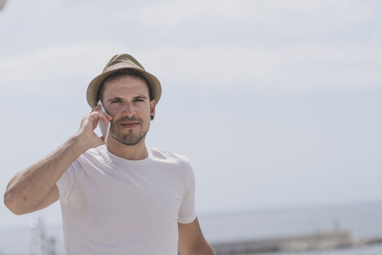Calling Casual Look Hat Man Beach Beard Casual Clothing Day Focus On Foreground Front View Leisure Activity Lifestyles Nature One Person Outdoors People Real People Sea Sky Smart Phone Standing Water Young Adult Young Men Young Women