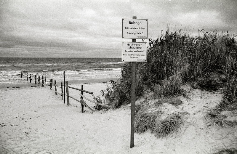 Bodstedter Bodden Analog Baltic Beach Beauty In Nature Blackandwhite Calm Cloud Cloud - Sky Coastline Day Dunes Film Horizon Over Water Idyllic Information Nature No People Outdoors Pole Sand Scenics Sea Shore Text Water