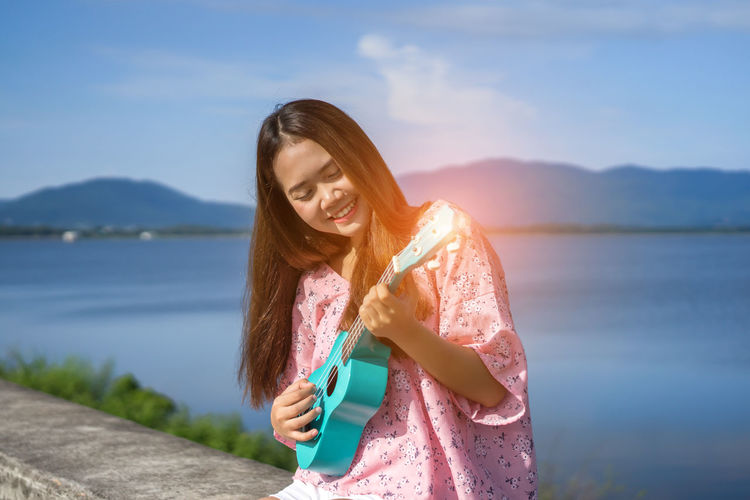Smiling young woman playing ukulele against lake and sky