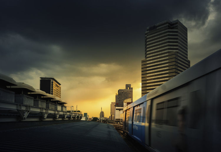 Modern buildings in city against sky at sunset
