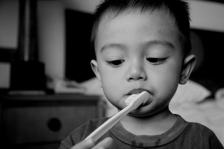 Close-up of cute boy brushing teeth at home