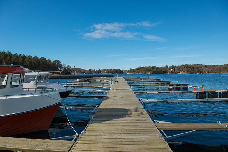 Pier over lake against blue sky