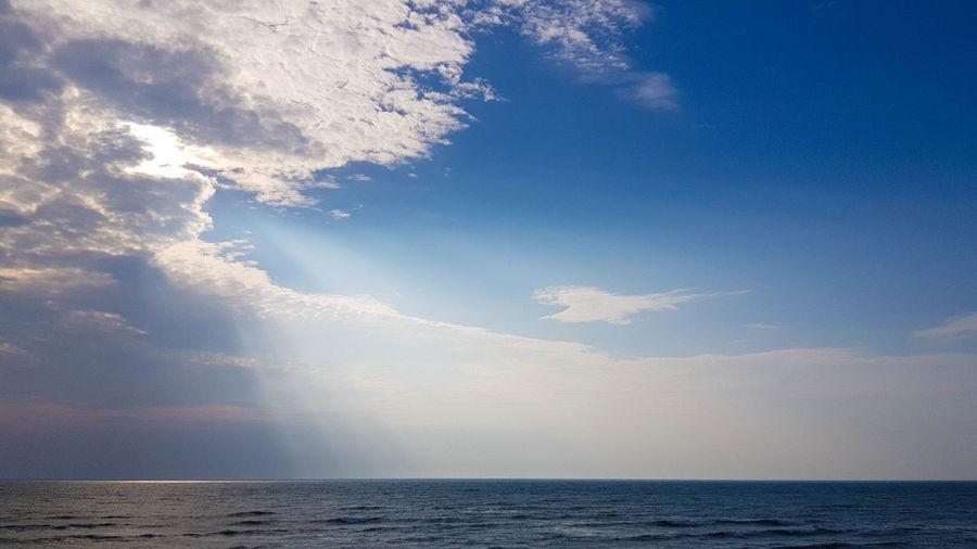 Sunlight streaming through sea against sky
