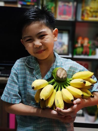 Portrait of boy holding bananas